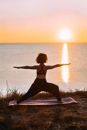 Vertical Yogi woman practices yoga at sunrise by the sea. Finding balance. Positive attitude, balance.