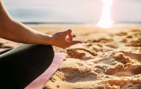 Yoga background. The girl sits on the beach by the sea in the lotus position. Side view. No face, hands, feet, sand. Meditation, balance, life balance, pacification, relaxation. High quality photo