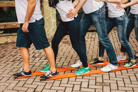 People stand with their feet on common wooden skis and move forward together. Teambuilding. High quality photo