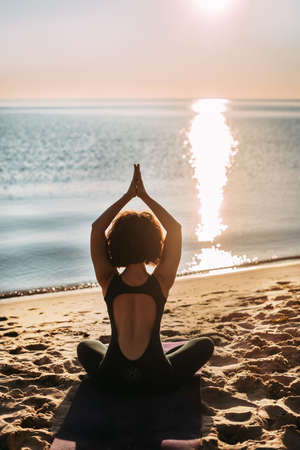 Yoga woman sits on the beach on the sand near the water in the lotus position with her hands raised up on a cushion and looks at the sunrise. High quality photo Standard-Bild