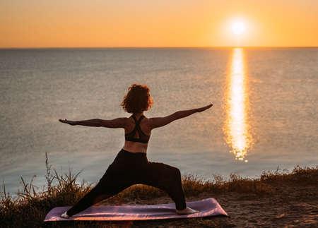 Yogi woman practices yoga at sunrise by the sea. Finding balance. Positive attitude, balance.