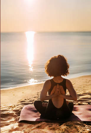 Yoga woman sits on the beach on the sand near the water in the lotus position with her arms crossed behind her back on a cushion and looks at the sunrise. Vertical photo