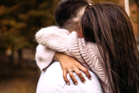 A woman hugs her beloved man very tightly in the park in the autumn forest. Autumn, love, relationship, missed, affection Standard-Bild
