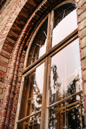 Vertical photo of a window in an old brick building with reflection of trees and sun