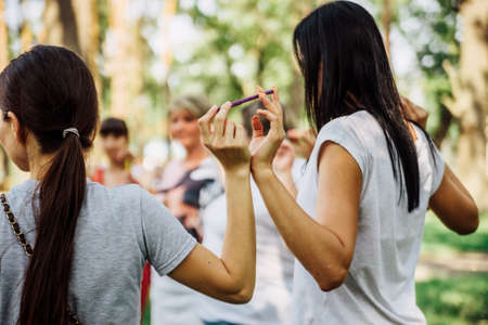 Exercise for team building employees. People stand in a circle and hold felt-tip pens with their fingers.