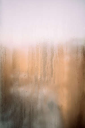 Vertical background texture of a wet window in drops with sun after rain. Warm photo