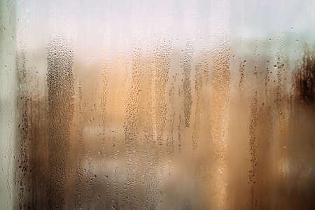 horizontal background texture of a wet window in drops with sun after rain. Warm photo