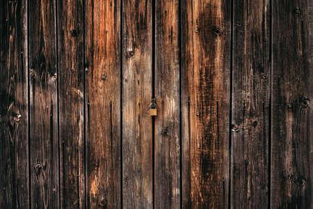 Textured wooden background dark brown fence with a lock. Standard-Bild