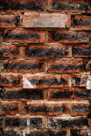 Vertical background of brick red with black painted burnt wall