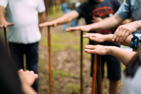 Close-up of the hands of people standing in a circle and holding sticks.