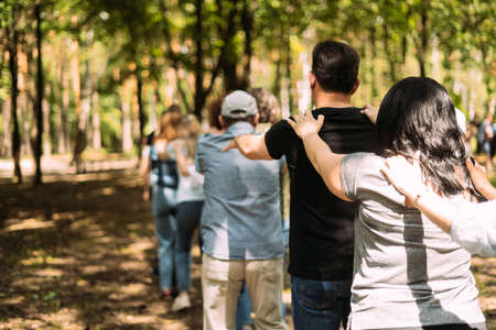 Team building exercise. People stand behind each other and hold their shoulders with their hands. Standard-Bild