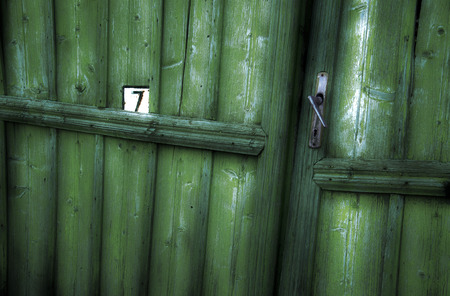 Number 7 written on an old weathered green door, vintage,