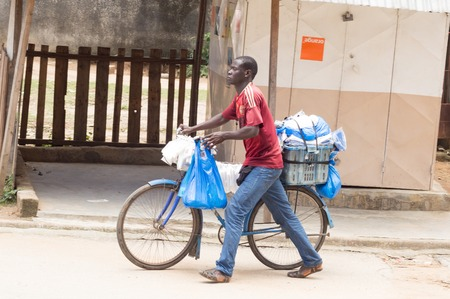 In ivory coast, in the neighborhoods peripherals that sellers are walking bags on their bikes in the streets to sell their wares. Éditoriale
