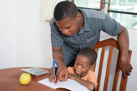escuela primaria: Su padre ayuda al ni�o a escribir en casa.