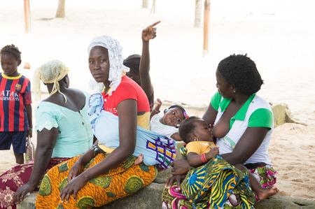 アビジャン、コートジボワール 8 月 29.2015: 若いアフリカの女性は彼女の赤ん坊を陰、1 つ breatsfeeding のココナッツの木の幹に座って、レビュー別彼
