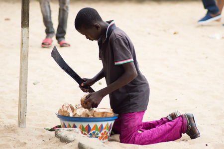 custumer: Abidjan, Ivory coast-august 29.2015: a young boy, machete in hand size was drowning coconut to sell it to a custumer Editorial