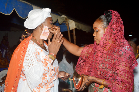 rejoicing: Abidjan, Ivory coast - February 26; 2015: Traditional rejoicing During the wedding ceremony in africa. The bride Gives banknotes to icts godmother. Editorial