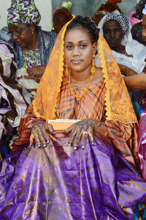 admire: Abidjan, Ivory coast - February 26; 2015: a young newly married woman is Being celebrated.Beautiful, this young woman sitting tattoo hands, well makeup, website and admire her wedding party,