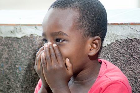 discreto: Este niño se esconde la boca con la mano, riendo y sigue siendo discreto. Foto de archivo