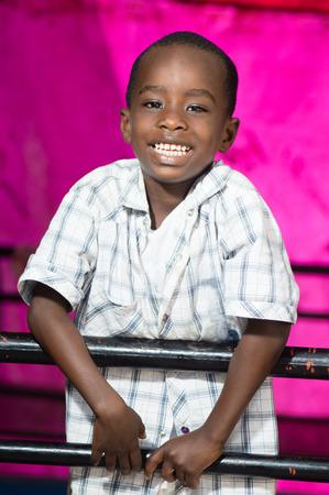 rejas de hierro: Este niño detrás de las rejas de hierro muestra su alegría reír.