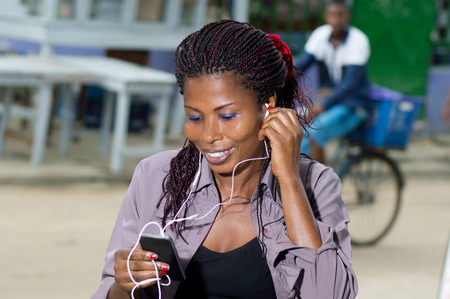 earpiece: This cheerful young woman, ALTHOUGH up her earpiece to hear better communication. Stock Photo