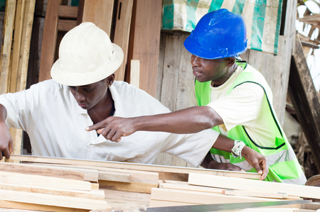 well made: The teacher teaches the student how to measure the boards to-have well made furniture.