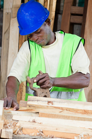 saved: The carpenter is Being saved planks piled before _him_.