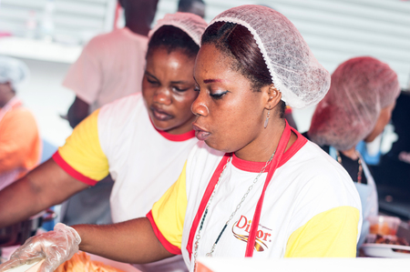obliged: Abidjan, Ivory Coast, September 11, 2016: the cooks in a restaurant When grilling festival of Abidjan. Women serve dishes to guests dressed in Their Obliged offert by Their sponsors Editorial
