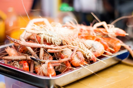 flesh eating animal: grilled shrimp in a tray on sale at a festival.