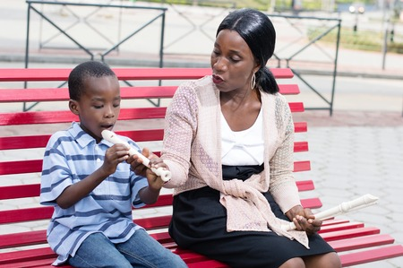 public space: woman teaches a child to play the flute ln public space.