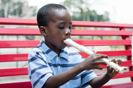 child sitting on the bench trains on flute. Stockfoto