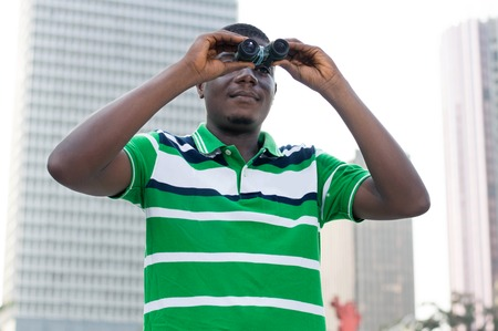 signify: young businessman looks through binoculars to signify That he is looking for paths to success.