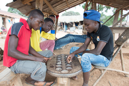 attended: Anekro, Ivory Coast - 27 August 2015: young playing the Awala  under a shed in the village. Four young men sitting under a shed in the morning indulge in a competition awale games