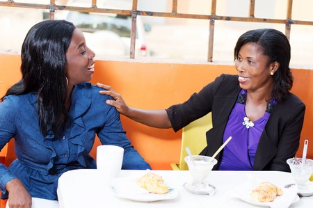two women sitting in a restaurant discussing in friendship around a lunch. Banque d'images