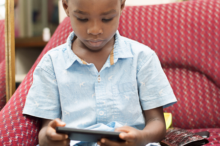 child is very Focus On His game in the mobile phone. Stock Photo