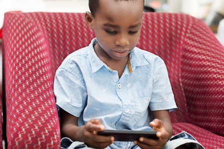 This child is very Focus On His game in the mobile phone.