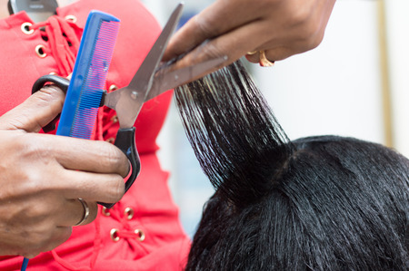 hairdresser arranges the hair of her customer by cutting with scissors em.