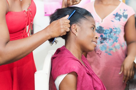 The hairdresser comb the hair of her customer before proceeding to put the shap of her hair.
