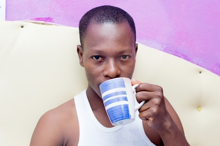 cheerful young man drinks coffee in bed Stock Photo