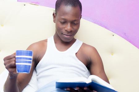 literas: Joven está leyendo en la cama con una taza de café en la mano para evitar el sueño.