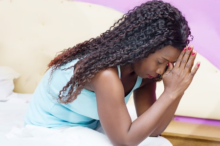 young woman sitting on the bed in her room praying.