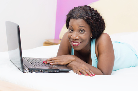 investigando: Smiling beautiful woman in front of her laptop in bed doing research Foto de archivo