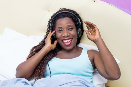 nightwear: Happy young woman listening to music lying in bed Stock Photo