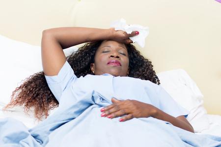Zieke Afrikaanse vrouw die in bed ligt dat witte zakdoek in hand houdt