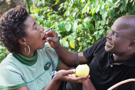 Happy couple in the countryside sharing fruit lovers