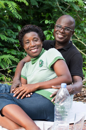 Portrait of happy loving couple sitting in the forest. Sitting on a white background smiling with her fiance Banque d'images