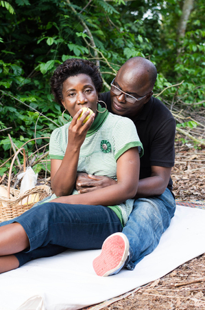 Love couple sitting on a mat in the bush. The man sitting behind his wife, looks her eat an apple.