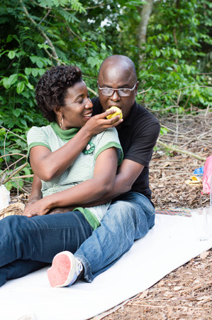 Young couple in love sitting on a piece of white cloth, is sharing an apple.