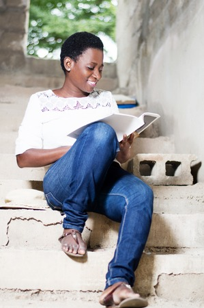 Beautiful young woman doing the reading on the stairs of an unfinished house.