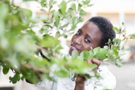 Young woman hidden behind the foliage to protect against the sun.